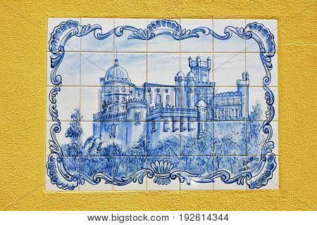 Sintra Portugal - June 03 2017: Blue azulejo panel of tiles in yellow plastered wall Sintra with the Pena National Palace