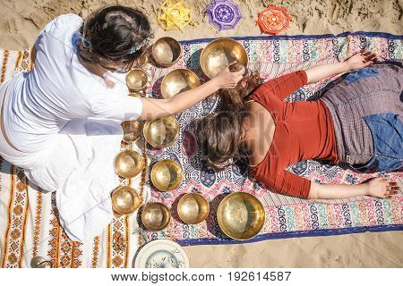 Woman Playing A Singing Bowls Also Known As Tibetan Singing Bowls, Himalayan Bowls. Making Sound Mas