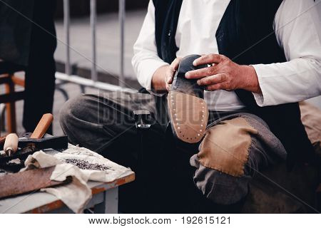 Master tailor makes shoes from leather. Concept of the old customs of making shoes and shoes.