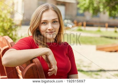 Cute Blonde Female With Appealing Eyes, Thin Lips And Freckles Wearing Red Sweater Resting Outdoors