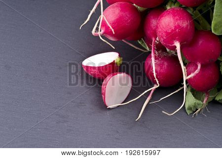 fresh raw spicy radish on slate background