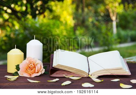 Open book candle and a fragrant rose. Romantic concept. A book with empty pages on the table. Copy space