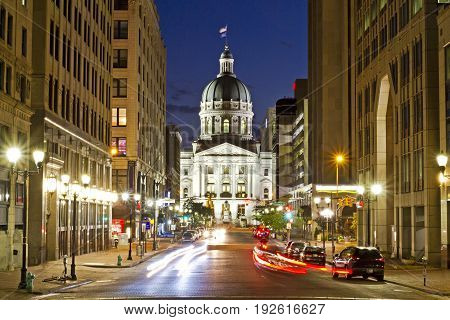 A dramatic view of the Indiana capitol building at night in Indianapolis with busy streets and a long exposure