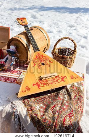 Balalaika and other products of Russian folk art over the snow background