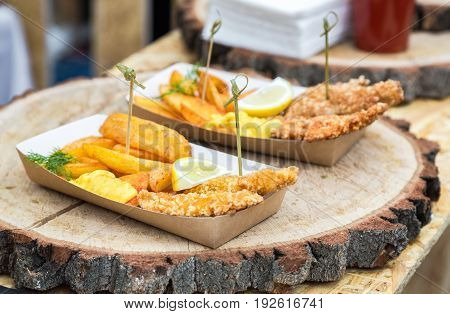 Fried potato and chicken meat with slice of lemon as creativity fast food