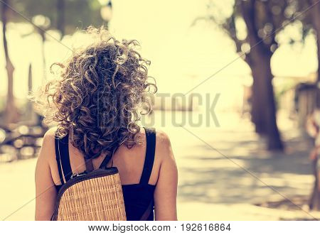 Woman seen from behind. Walking on a path toward an uncertain future but bright. Conceptual image.