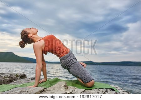 Young sporty woman doing different variants of yoga position on a rocky rivershore. Beauty woman dressed in the sportwear and barefoot. Beautiful landscape like a background. Concept of the healthy and active lifestyle.
