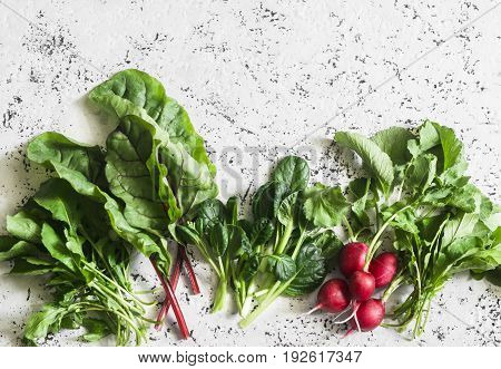 Range of herbs salad ingredients - radishes swiss chard arugula spinach. On a light background top view. Free space for text. Flat lay
