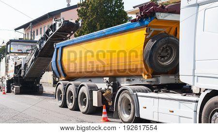 Road construction asphalt paving of a road. Dumper truck is loaded with asphalt milled from cold planer machine.