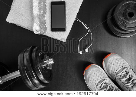 Fitness concept. Sport equipment. Sneakers (sport shoes) towel bottle of water earphones dumbbells and phone on black background.