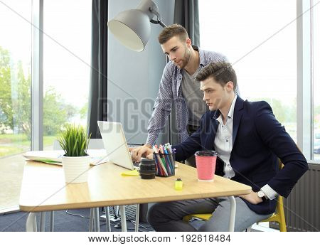 Two young modern men discussing work in the office studio