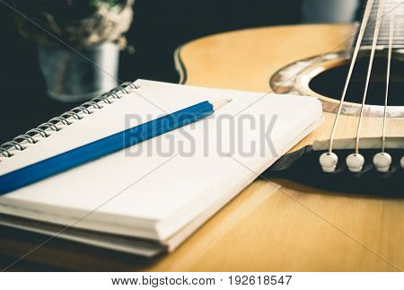 Pencil and Notebook on Acoustic guitar for songwriter