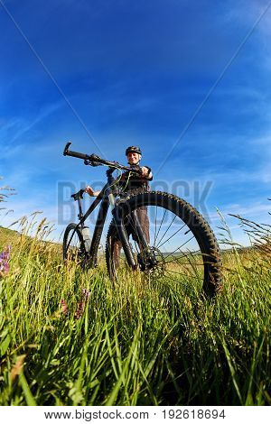 Young cyclist in the helmet in the green meadow on a background with blue sky. Sportsman dressed in the black sportwear and sporty shoes, with backpack. Vertical photo and fisheye. Concept of the healthy and active lifestyle.