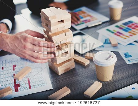 Businessmen working together to build a small construction of wooden toy. Concept of teamwork, partnership, integration and startup.