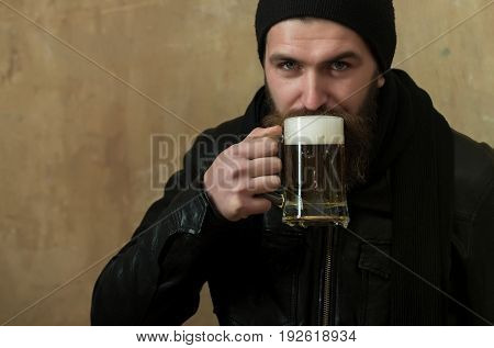 hipster with long beard and moustache drinking beer with foam from glass mug in black hat and jacket on beige wall. Alcohol bad habits addictive lifestyle refresher convive
