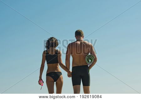 couple in love of sexy man with muscular body and torso hold dumbbell and fitness mat in athletic hand and girl with water bottle on blue sky sport and health workout and energy