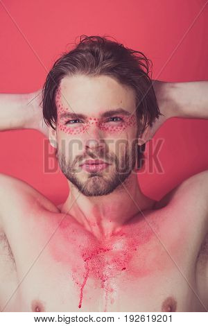 guy or handsome man with creative fashionable makeup on face on red background beauty and fashion allergy