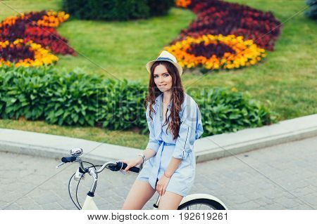 Charming young woman on bike in city