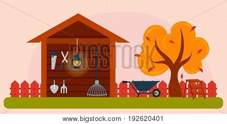 Autumn garden landscape. Yellow tree with stairs and cart wooden hangar with garden equipment