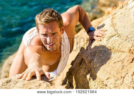 Male climber climbing on the rocks against sea water. Rockclimbing guy in swimwear reaching for a next stone grip on a steep mountain. Summer activity extreme sports outdoors