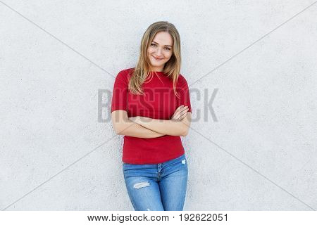 Lovely Female In Red Sweater And Jeans Standing Crossed Hands Against White Wall Looking Directly In