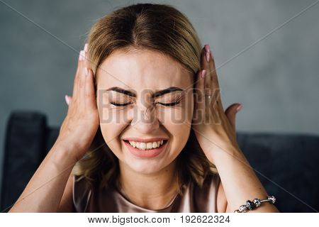 Happy woman covering her ears with hands. The girl expresses various emotions