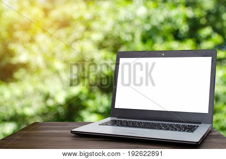 Laptop computer with white blank screen on wooden table with blurred nature green bokeh background selective focus copy space business working outdoor online social media searching data concept