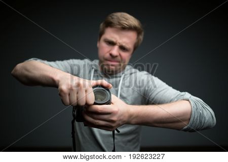 Handsome photographer with camera in photo studio try to put out photo filter form lens