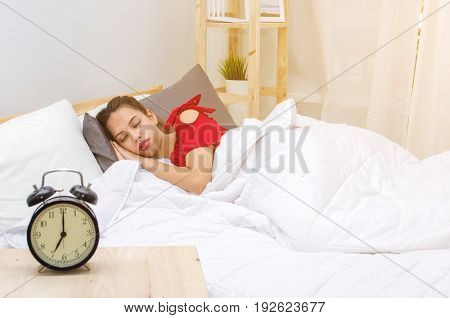 A asian young woman in red pajamas sleeping on bed and alarm clock in bedroom at the morning selective focussunlight effect