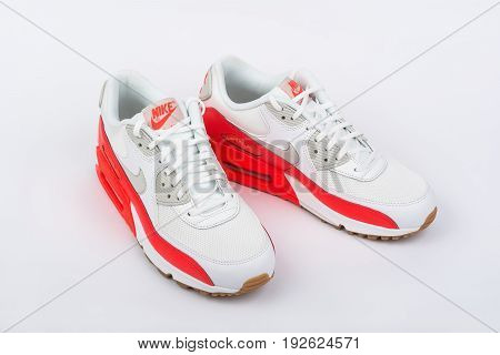 BURGAS, BULGARIA - AUGUST 29, 2016: Nike Air MAX women's shoes - sneakers - trainers in white and orange on white background. Nike is a global sports clothes and running shoes retailer.