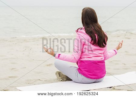 woman practices yoga and meditates in the lotus position on the beach.