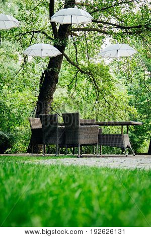White umbrellas hang on trees and wicker furniture stands in the garden
