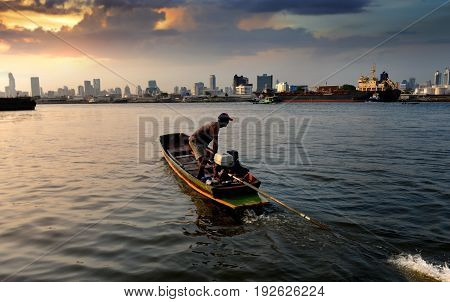 Silhouette of longtail boat with driver on Chaopraya river in Bangkok photo in sunset time lighting very low light and dark
