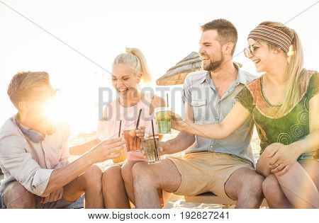 Happy friends group having fun at beach party drinking cocktail at sunset - Summer joy and friendship concept with young people on vacation - Warm sunshine filtered color tone with focus on blond girl