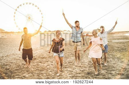 Group of happy friends having fun on the beach at sunset - Summer joy and friendship concept - Warm sunshine filtered color tone with focus on tall guy in the middle holding sparkle bengal fire candle