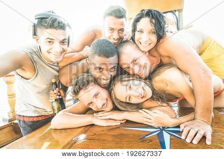 Group of best friends guys and girls taking selfie at sailing boat - Happy youth friendship concept with young multiracial people having fun together at summer beach vacation - Bright backlight filter