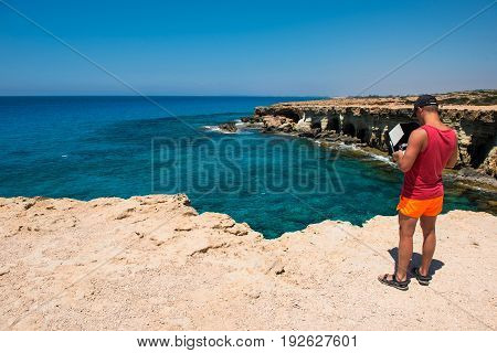 AYIA NAPA CYPRUS JUNE 15 2017: Guy flying and making an aerial video with a DJI Phantom Pro 4 drone above the sea caves of Ayia Napa Cyprus