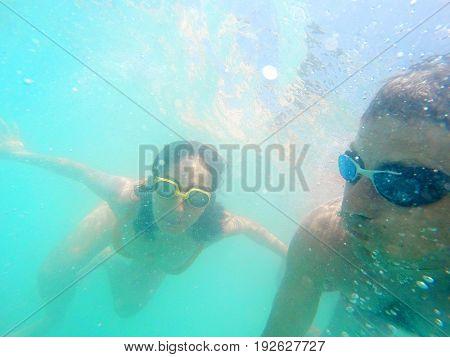 Couple Having Fun Underwater In The Sea