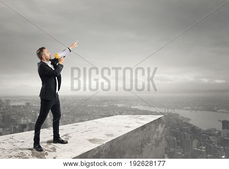 Businessman authoritarian announcement to the megaphone from above a roof