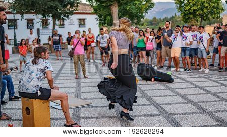 GRANADA, SPAIN - JUNE 23: Unidentified flamenco dancer dances for tourists in St. Nicolas viewpoint to Alhambra in Granada on June 23, 2017 in Spain