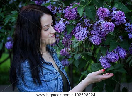 Young beautiful girl close-up stands on a background of beautiful and fragrant lilac.