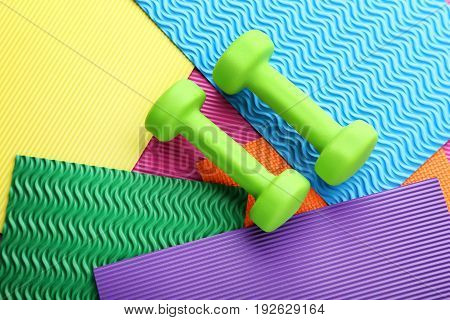 Green dumbbells on colorful background, close up