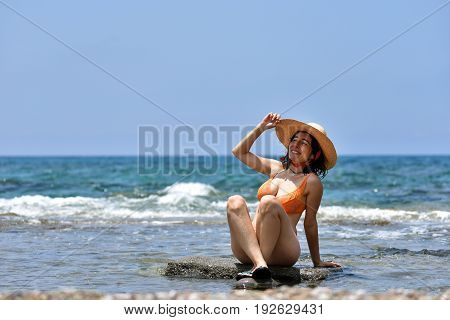 Sexy Bikini Tanning Woman Relaxing On The Beach With A Hat