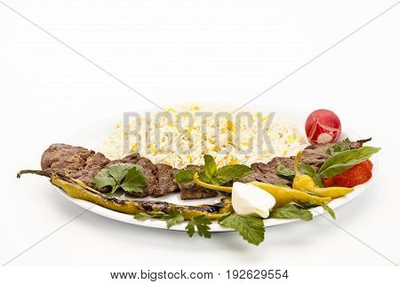Studio shot of grilled lamb kebab with rice served on plain plate. Low angle view closeup on white table top. Fusion food concept for Persian cuisine barbecue Middle Eastern dining and hearty meal.