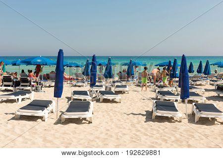 Tourists Relaxing On Sunbeds On A Sandy Beach Under Beach Umbrellas