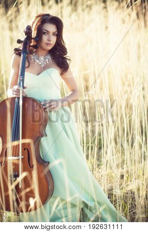 A girl in a green dress with a cello on a yellow cane background
