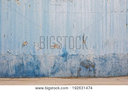 abandoned grunge cracked stucco wall and tiled footpath
