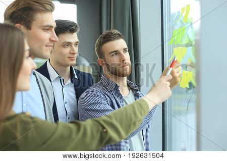 young creative startup people on meeting at modern office making plans and projects with post stickers on glass