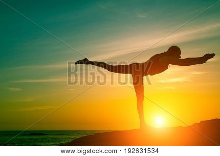 Yoga and healthy lifestyle. Silhouette of fitness woman doing exercises on the sea beach during amazing sunset.