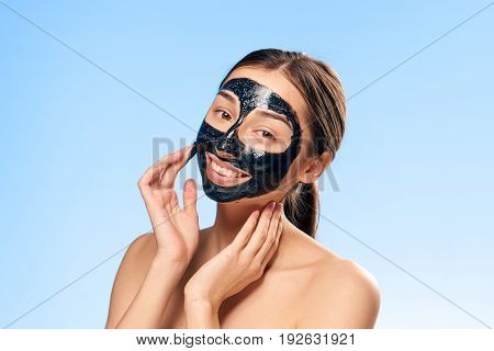 Cosmetic mask, woman in cosmetic mask, woman on blue background.